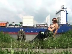 Fat woman outside flashing a cargo ship