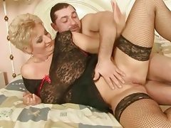 Grandma in fishnet stockings enjoys..